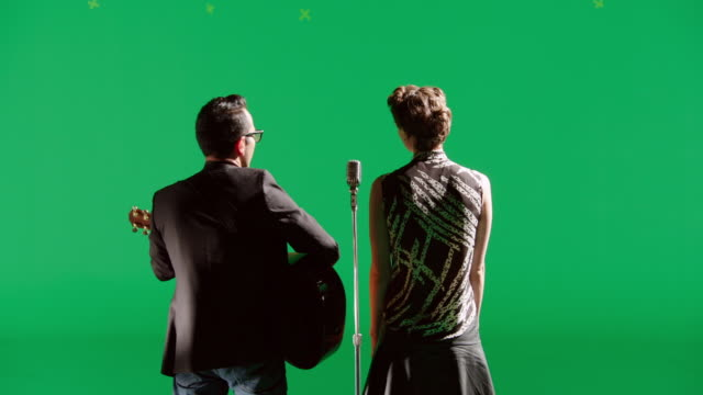 MS Back of duet singing and playing the guitar in front of green screen