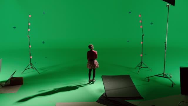 vídeos y material grabado en eventos de stock de cs back of girl singing in front of green screen - plató de cine