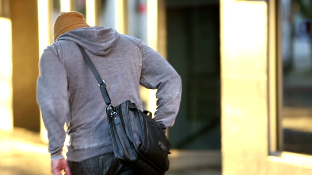 back of hispanic man walking in the city - hands in pockets stock videos & royalty-free footage