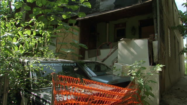 vidéos et rushes de hd back of home w/ back porch covered w/ large square objects cinder block holding trunk of one of the two cars down mesh fencing connected to other... - parpaing