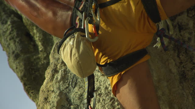 cu back of man climbing rock face and dipping hand in chalk-bag / krabi, thailand - hex climbing equipment stock videos and b-roll footage