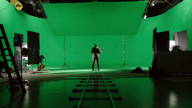vídeos de stock, filmes e b-roll de ds back of man singing in front of green screen - câmera em movimento