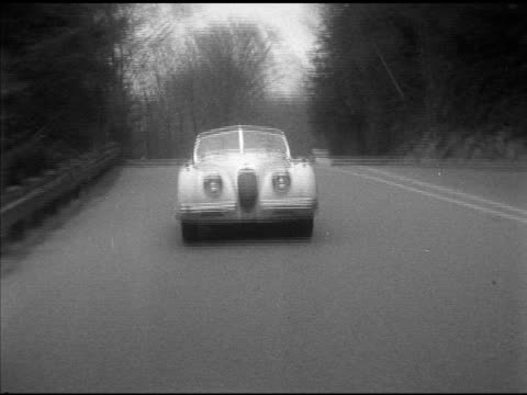 stockvideo's en b-roll-footage met 1953 jaguar xk120 convertible driving down road shaky taking road bumps ms 'cass' driving ws approaching passing sedan under old arched overpass - shaky