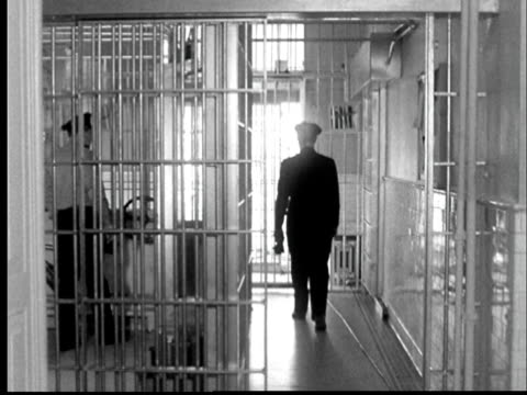 1956 ws back of police officer walking through prison cell gate as guard closes gate behind him at kansas state penitentiary/ lansing, kansas - leaving prison stock videos & royalty-free footage