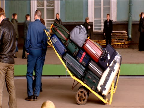 back of porter with trolley full of luggage leaning against him russian train station - full stock videos and b-roll footage