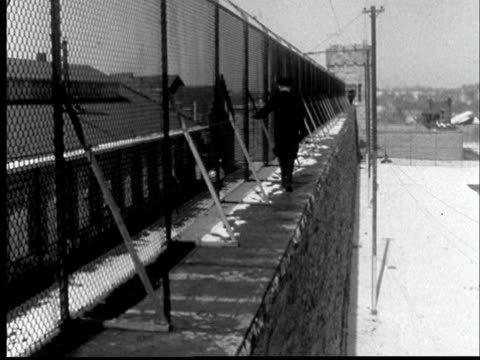 1956 ws back of prison guard walking on top of prison wall on watch at kansas state penitentiary/ lansing, kansas - high up stock videos & royalty-free footage