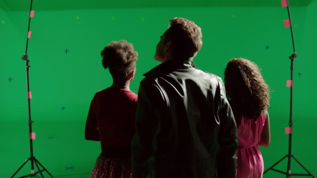 MS Back of trio singing in front of green screen