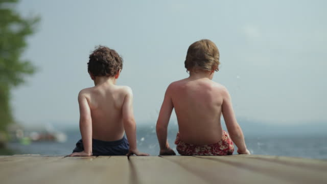 ms back of two boys sitting and looking at water and kicking water on dock / wolfebro, nh, usa    - children only stock videos & royalty-free footage