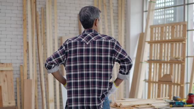 vidéos et rushes de dos de vue, homme aîné asiatique âgé 61 ans il est charpentier stand whie regardant par la fenêtre penser à quelque chose de trouver une solution. grey power - concept d'entreprise senior. - bricolage