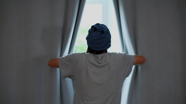 stockvideo's en b-roll-footage met terug van jonge aziatische man onthullen gordijn en kijken uit raam terwijl staan in bed kamer in de ochtend, slow motion - gordijn