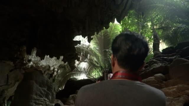 vídeos de stock, filmes e b-roll de parte traseira do jovem viajante está na caverna na floresta antiga, uthaithani, tailândia - pouca luz