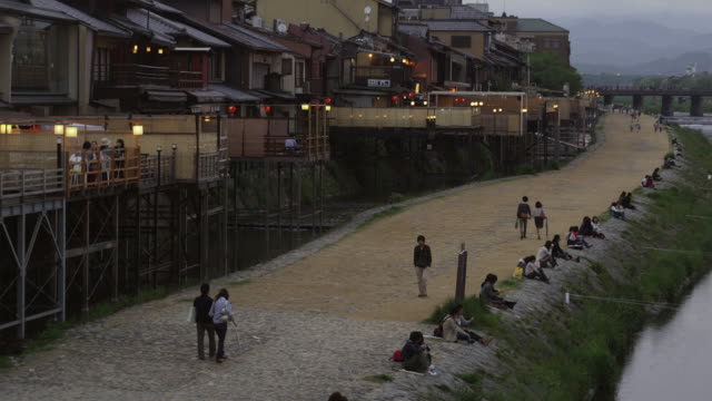 ws ha back part of pontocho alley and promenade at kamo river at dusk, kyoto, japan - riva del fiume video stock e b–roll