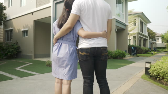 back portrait of asian young couple standing and hugging together looking happy in front of their new house to start new life. family, age, home, real estate and people concept. - young couple stock videos & royalty-free footage