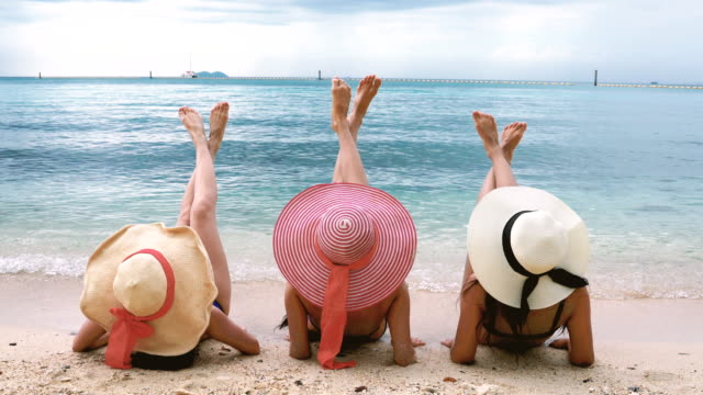back rear view of three girls lying on beach raising legs - sunbathing stock videos & royalty-free footage