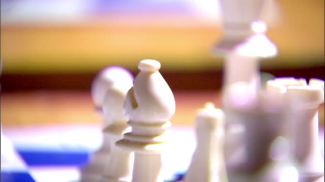 back row of game playing pieces male hand moving soft focus bishop in focus bishop playing piece w/ queen fg rook bg - chess piece stock videos & royalty-free footage