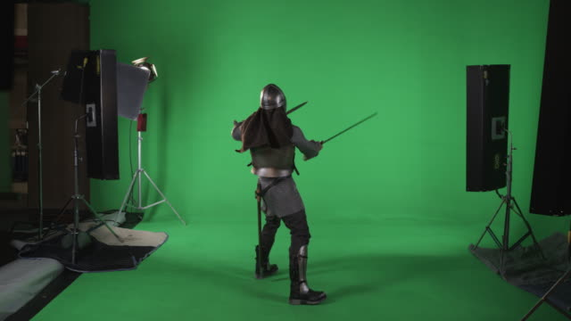 back shot of man in armor with sword and short sword. shot in slow motion against a green screen. - warrior person stock videos & royalty-free footage