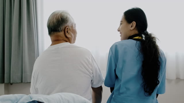 back shot of nurse talking to senior man at home. - 70 79 years stock videos & royalty-free footage
