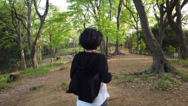 vidéos et rushes de dos tourné de jeune femme exécutant dans le parc - habillement