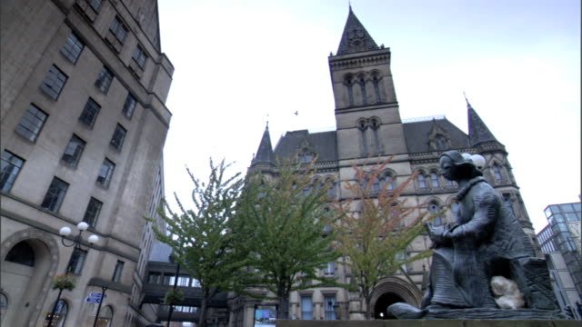 vídeos de stock e filmes b-roll de back side of manchester town hall partial manchester visitor information centre building trees statue of female sitting lower frame fg - town hall