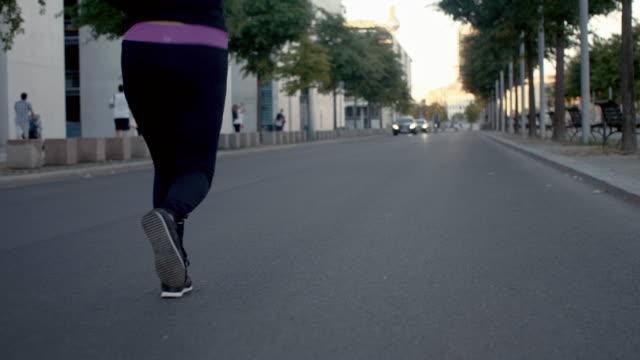 vídeos de stock, filmes e b-roll de vista do lado traseiro da mulher muçulmana em hijab executando em berlim (câmera lenta) - vestuário modesto