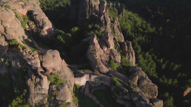 back to nature. aerial view over a tourist hiking in the red rocks of belogradchik mountains. enjoyment outdoors on a sunny day during the covid-19 pandemic. unesco world heritage site. - bulgaria stock videos & royalty-free footage