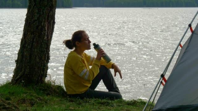stockvideo's en b-roll-footage met terug naar de natuur. individuele reiziger. panoramisch uitzicht op een gelukkige jonge vrouw toeristische camping in de natuur. op een zonnige dag buiten in de bergen genieten. - sunny