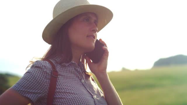 vídeos y material grabado en eventos de stock de de vuelta a la naturaleza. mujer viajera solo hablando por teléfono con alguien mientras está en la naturaleza. disfrute al aire libre en los campos de hierba verde en un día soleado. - área silvestre