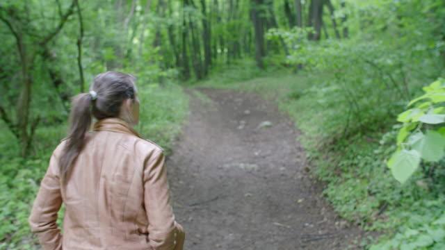 stockvideo's en b-roll-footage met terug naar de natuur. vrouw solo traveler wandelen in de natuur. genieten buiten in de bossen op een zonnige dag na de covid-19 quarantaine einde. - verwonderingsdrang