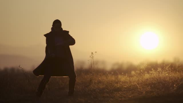 zurück zur natur. junge frau übt tai-chi in den frühen morgenstunden bei sonnenaufgang licht. ws eines fröhlichen mädchens, das entspannungsübungen in der natur macht. - asiatischer kampfsport stock-videos und b-roll-filmmaterial