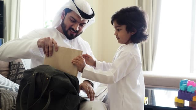 Back to school time: arab dad and son preparing the backpack