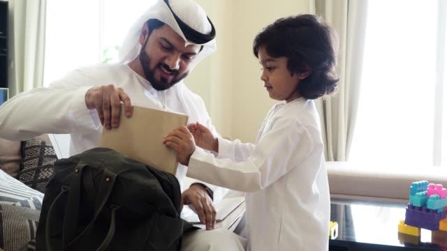 学校の時間に戻って: アラブお父さんと息子のバックパックを準備 - 頭にかぶるもの点の映像素材/bロール