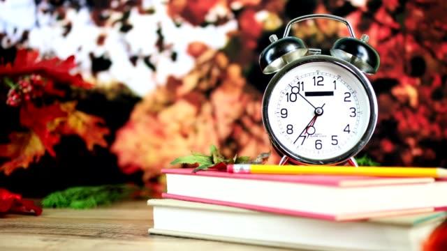 back to school with alarm clock in autumn season. - riapertura delle scuole video stock e b–roll