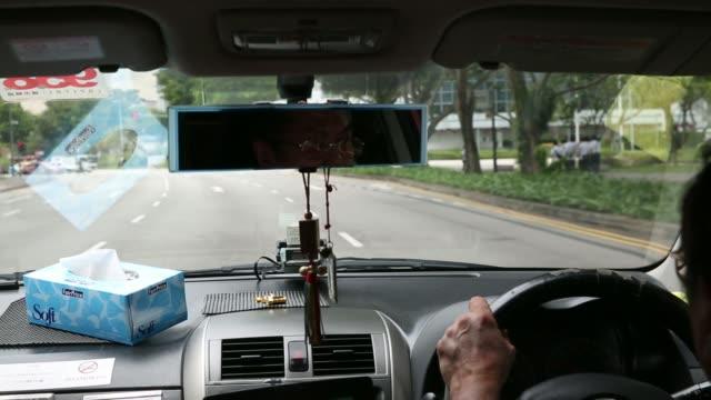vídeos y material grabado en eventos de stock de back view a taxi driver driving cab along roads through singapore, on monday, dec. 9, 2013 singapore taxi driver on december 09, 2013 in singapore,... - taxista