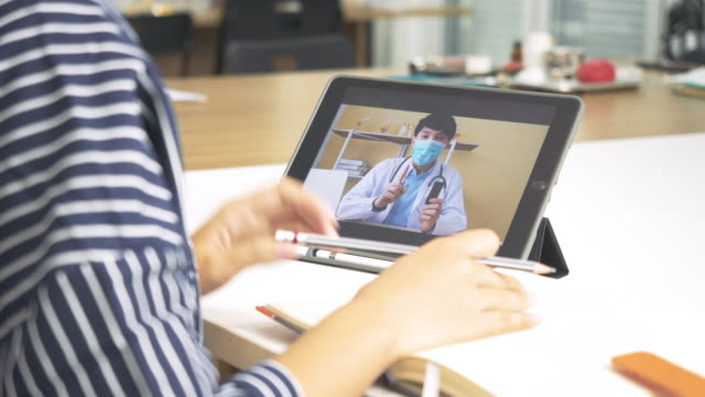 back view asia woman video call with man doctor while staying at home. patient in video conferencing with general practitioner on digital tablet. doctor online technology concept. - working in remote location stock videos & royalty-free footage