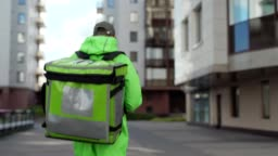 Back view follow shot of young male food courier in green uniform using mobile app on smartphone while walking down street with insulated backpack delivering food. Man coming to building door