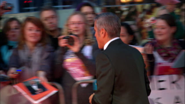 back view George Clooney signing autographs for clamoring fans behind barricades along red carpet
