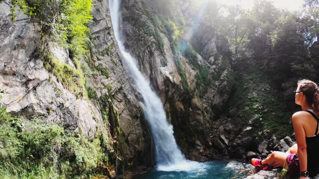 back view of a woman sitting on a rock by a beautiful waterfall - abseiling stock videos & royalty-free footage