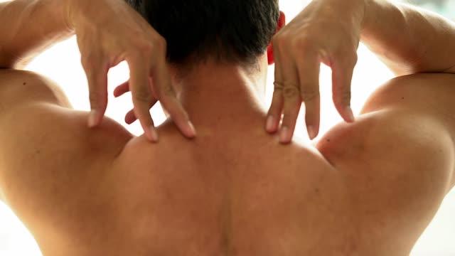 Baksidan på en ung man att röra hans hals med handen stående isolerad på vit bakgrund. Attraktiva skäggiga hipster lider av nacksmärta. Massage, sjukgymnastik och hälso-och begrepp.