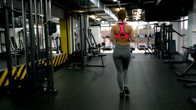back view of an athletic woman entering the gym and going towards the exercise machine and start exercising. - lateral pull down weights stock videos & royalty-free footage