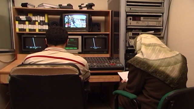 back view of an editor and a female journalist creating a news reportage at al-manar tv. al manar television is a lebanese satellite tv station... - editor stock videos & royalty-free footage