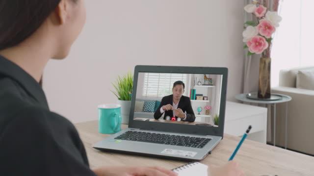 vídeos de stock, filmes e b-roll de visão de trás da mulher de negócios asiática falando com seus colegas sobre o plano em videoconferência. equipe de negócios multiétnica usando computador para uma reunião on-line em chamada de vídeo. grupo de pessoas inteligentes trabalhando em ca - entrevista formato bruto