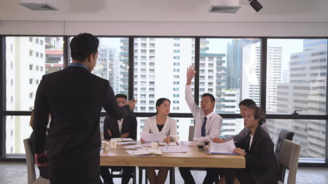 back view of asian businessman coaching and presenting to businesspeople in modern workplace. employees raise hand to ask question - rules stock videos & royalty-free footage