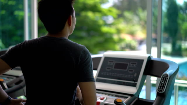 Back view of Asian man running on treadmill in gym with swimming pool nature background