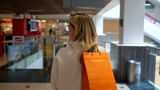 vídeos de stock e filmes b-roll de back view of blond woman walking at the mall looking at different sides while carrying a paper bag - viciado em compras