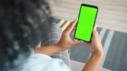 Back view of brunette holding chroma key green screen smartphone watching content