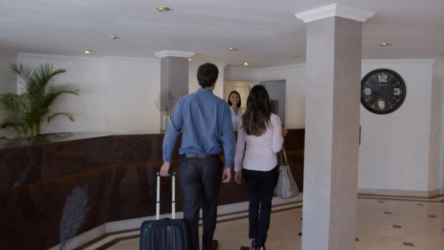back view of business couple arriving to the hotel ready to check in - checkout stock videos & royalty-free footage