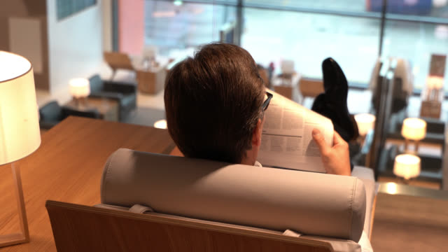 back view of business man relaxing at the airport's vip lounge reading a news paper - gate stock videos & royalty-free footage