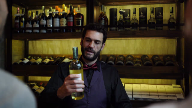 フレンドリーな男性レジにチェックアウト時にボトルを支払うワインセラーでカップルのバックビュー - ワインバー点の映像素材/bロール