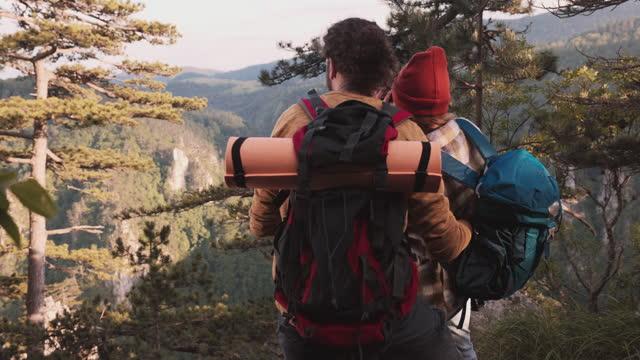 back view of couple of young hikers enjoying the beautiful view together. - sunday bildbanksvideor och videomaterial från bakom kulisserna
