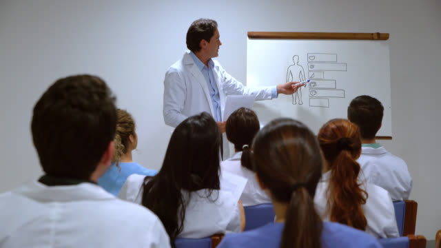 back view of doctors at a hospital tending a class with head doctor - civilian stock videos & royalty-free footage